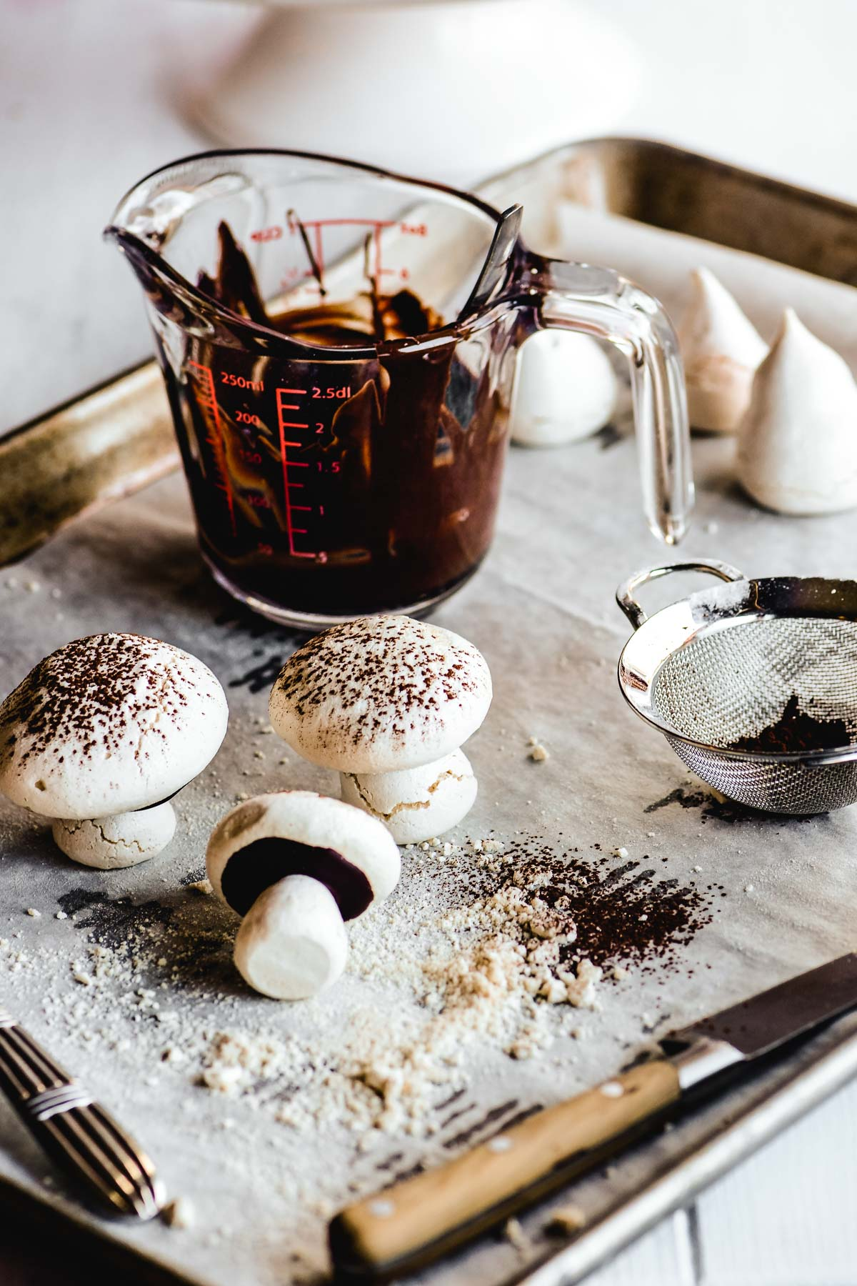 Using melted chocolate to 'glue' together meringue mushroom cookies