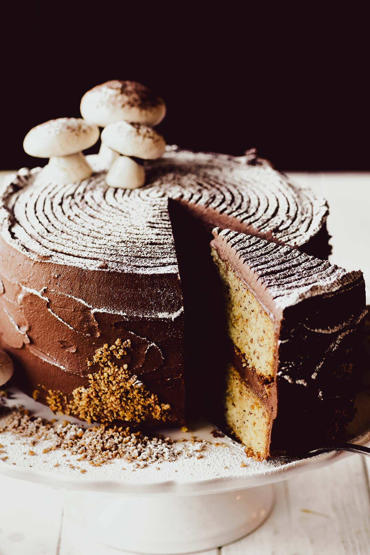 buche de noel layer cake on a cake stand with meringue mushrooms