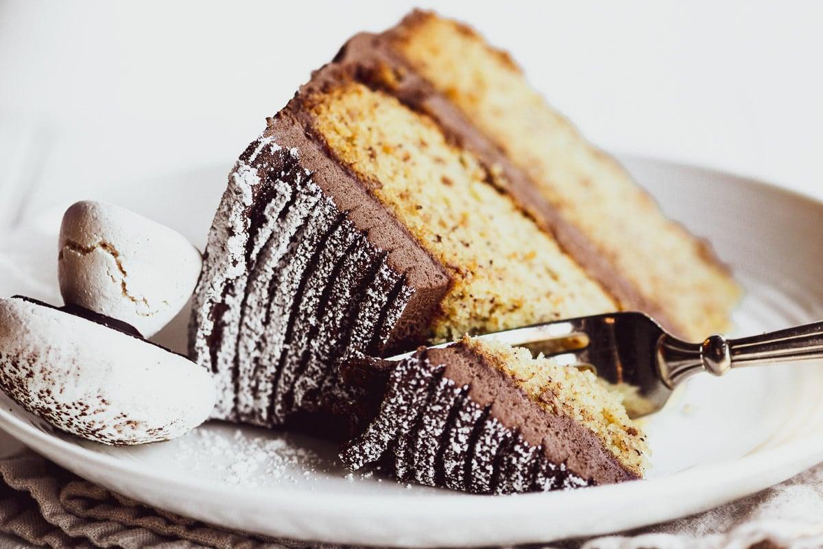 Taking a bite of a chocolate hazelnut layer cake