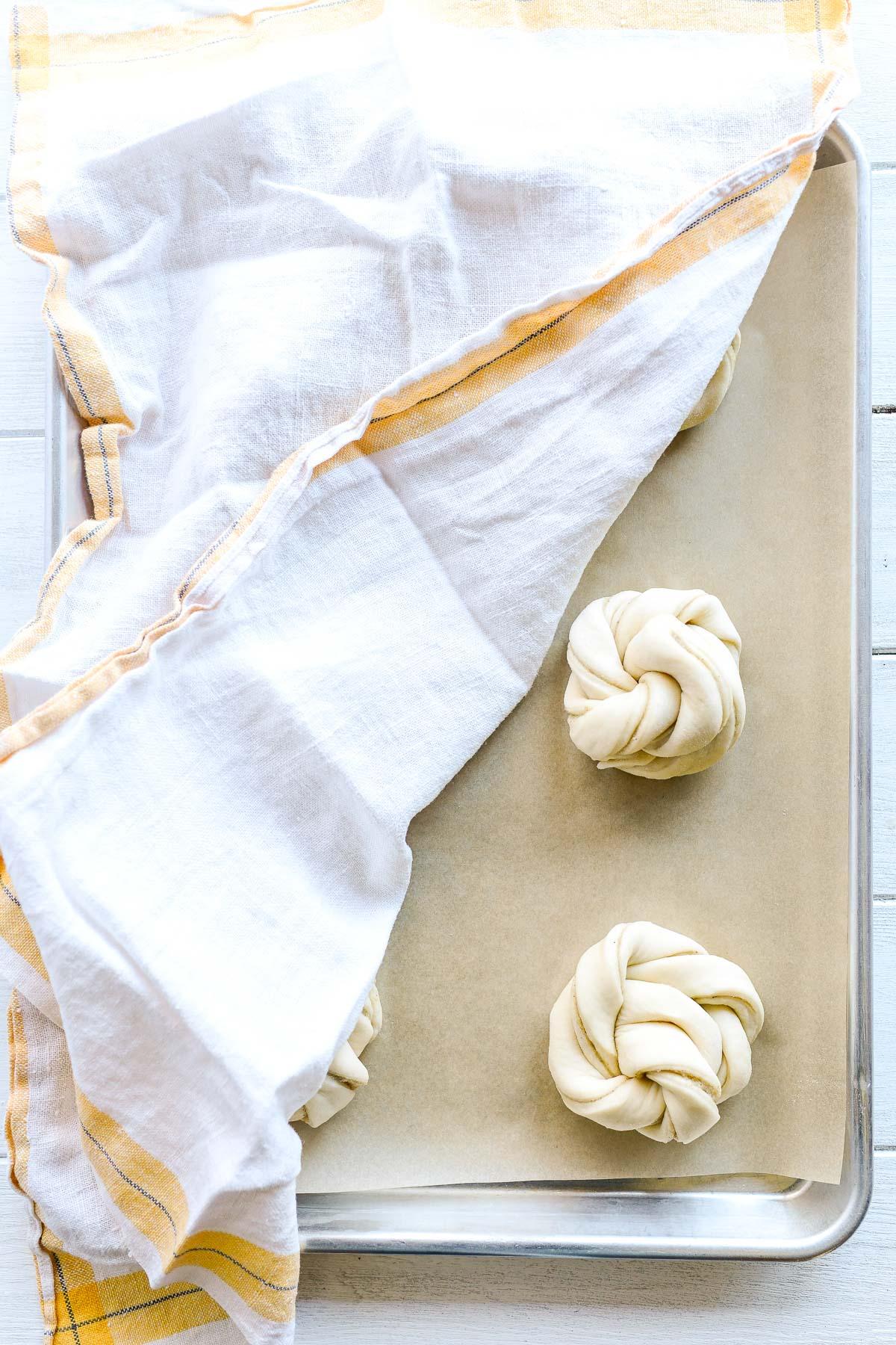 cardamom buns resting on a baking sheet
