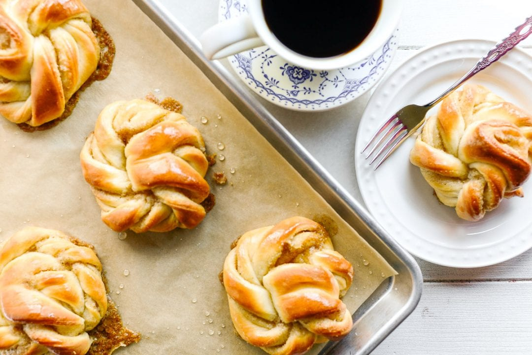 cardamom buns on a baking tray with cup of coffee