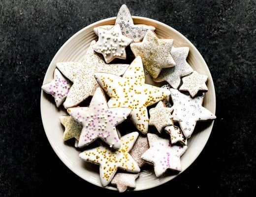 A plate of gingerbread star cookies with sprinkles