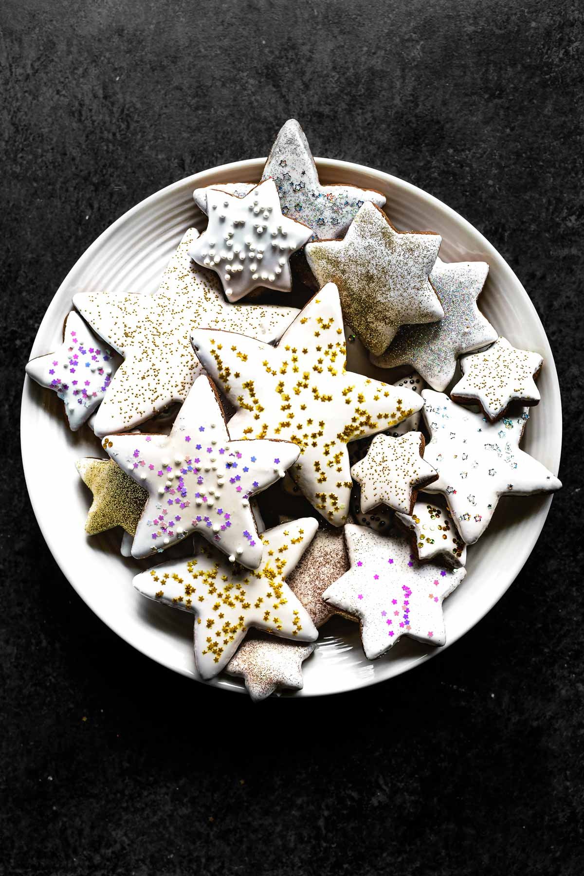 A plate of gingerbread star cookies with sprinkles on a black background