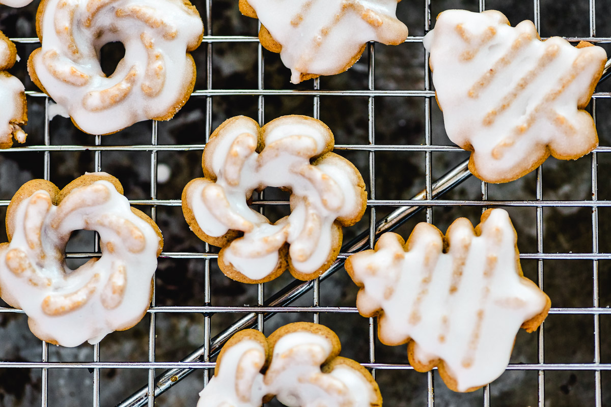 glazed gingerbread spritz cookies on a baking rack