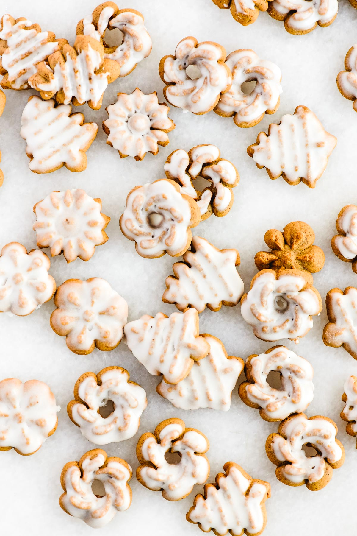 glazed gingerbread spritz cookies on a marble slab