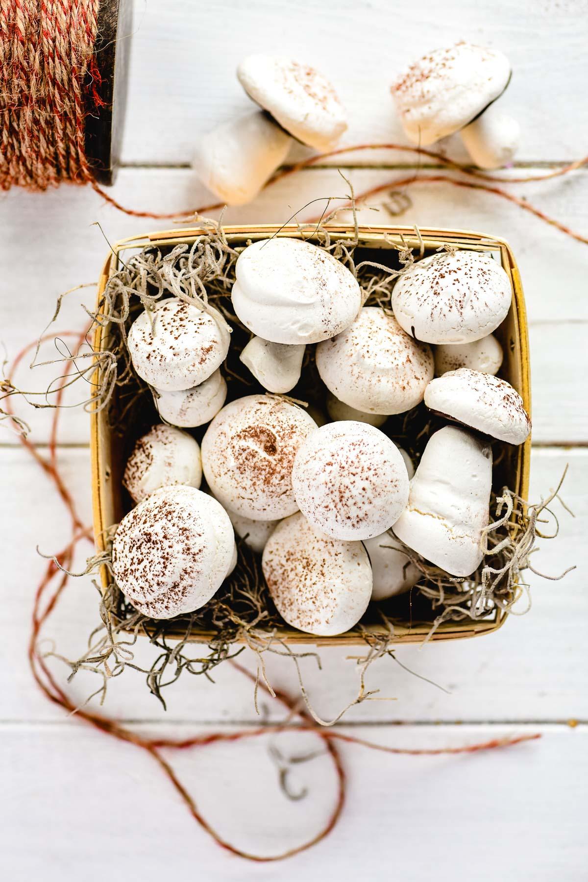 meringue mushroom cookies in a basket with twine