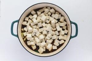 adding tofu to the pan for mapo tofu recipe