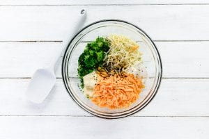 Ingredients for baked broccoli cheese dip in a glass mixing bowl