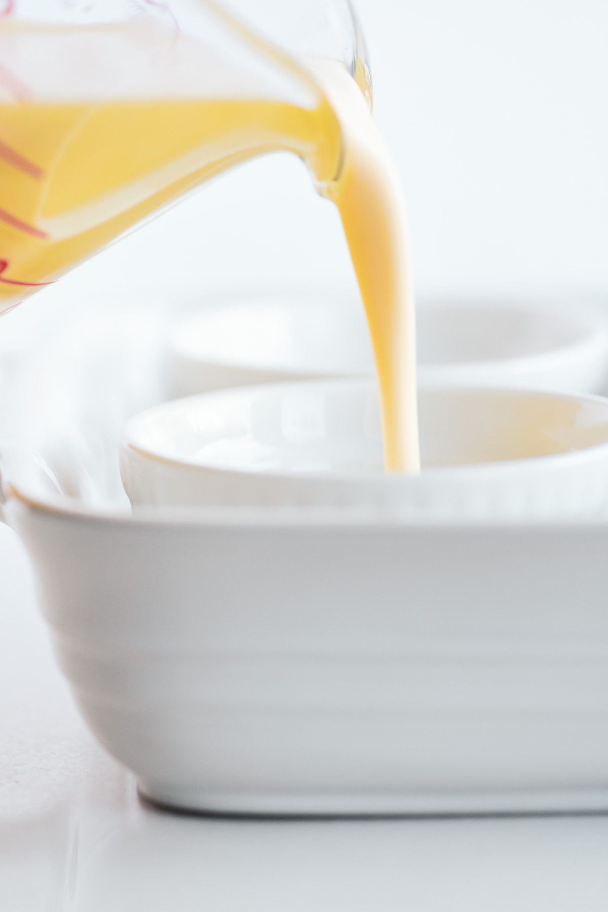 pouring custard batter into small custard cups