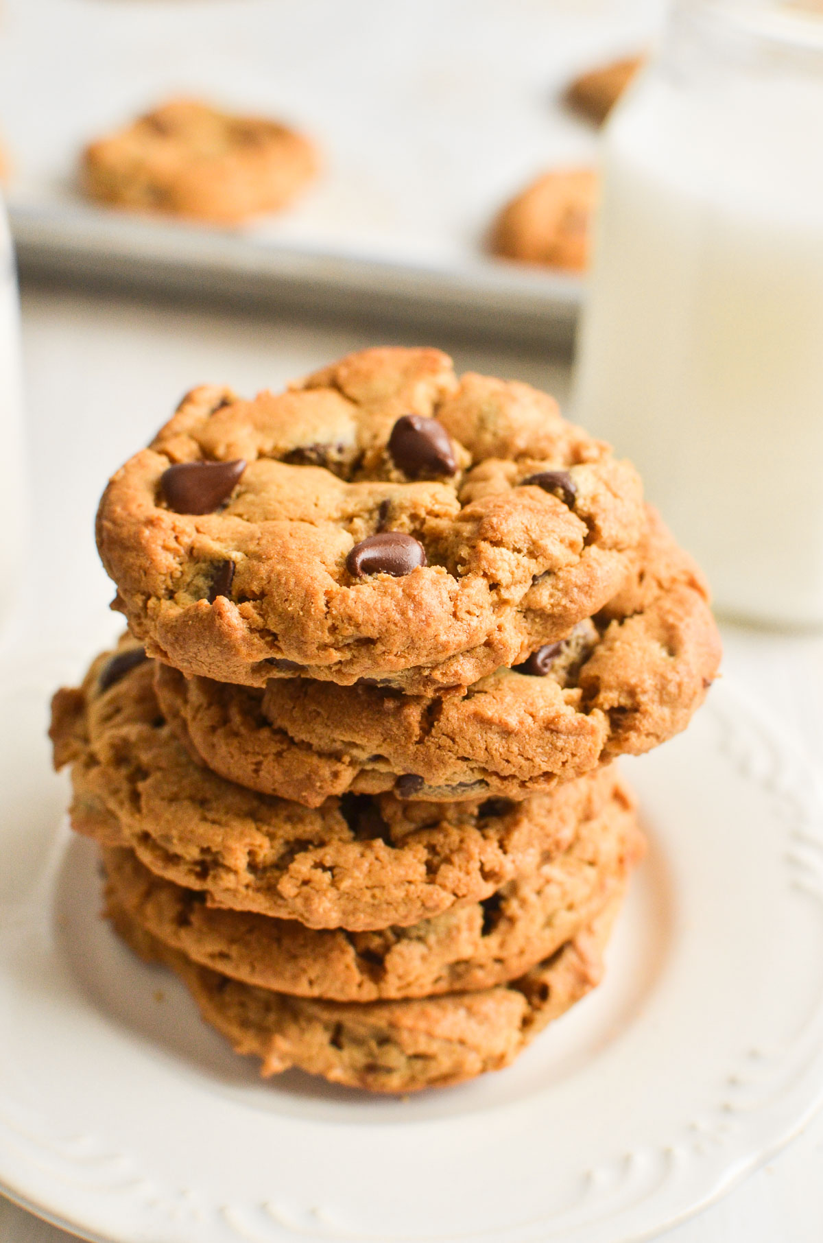 A stack of flourless peanut butter chocolate chip cookies on a white plate.