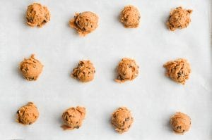 cookie dough scooped out onto parchment paper