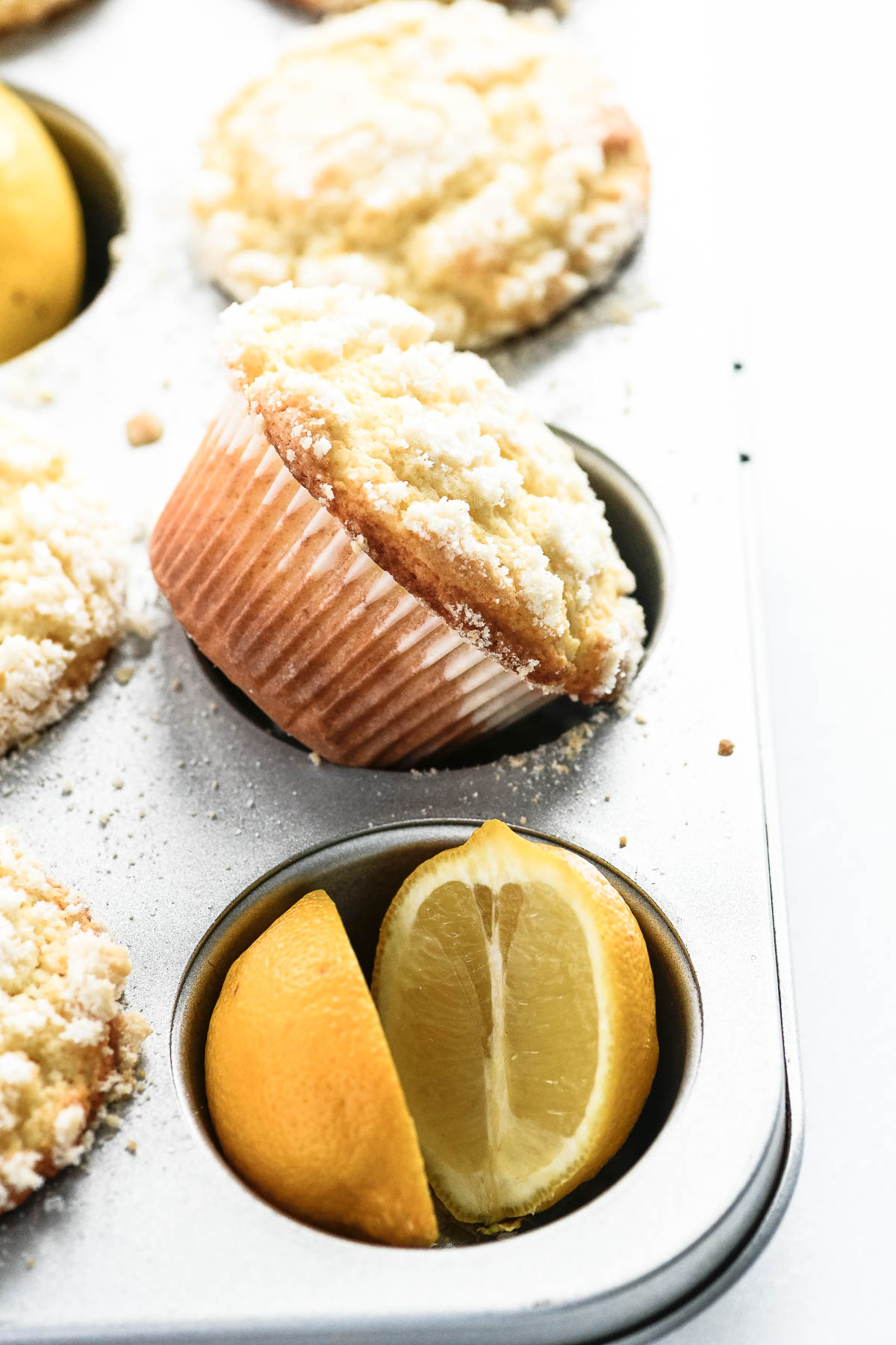lemon streusel muffins in a muffin pan with fresh lemons