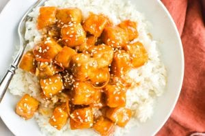 orange tofu with rice, in a bowl