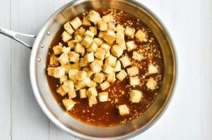 Adding baked tofu cubes to orange sauce