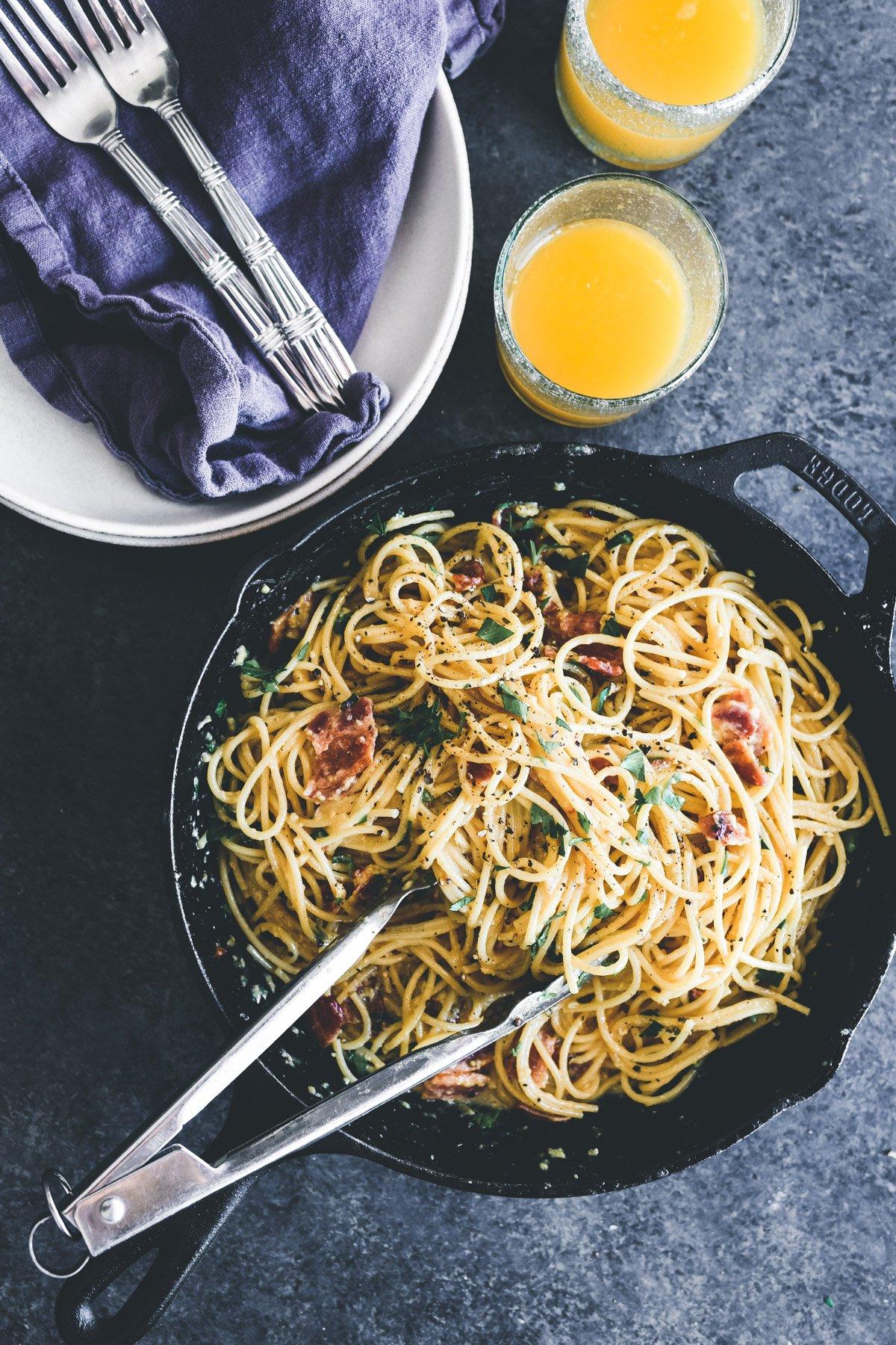 a skillet of breakfast pasta with orange juice