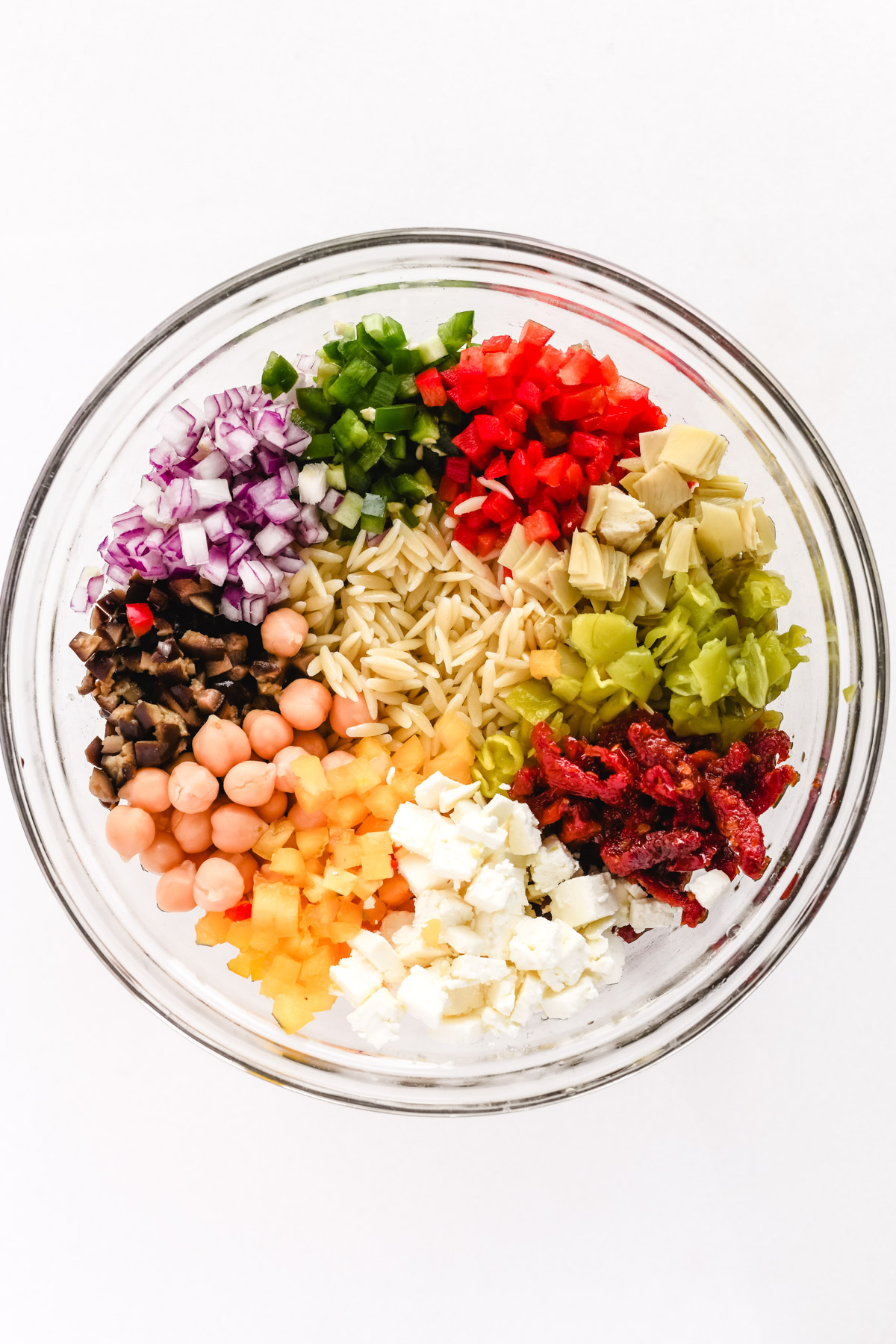 ingredients for Mediterranean orzo salad in a glass bowl
