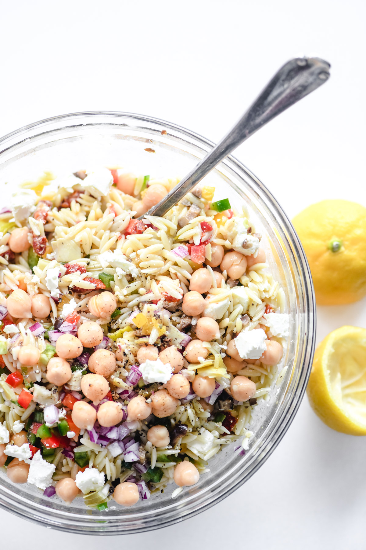 a glass bowl of Mediterranean orzo salad with spoon