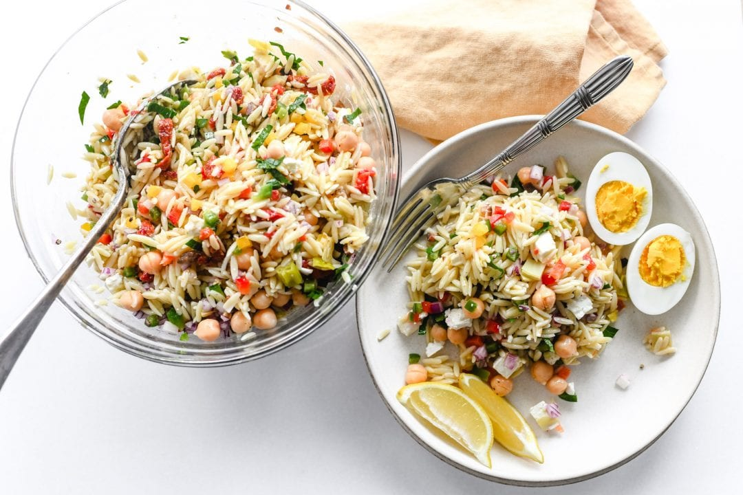 A bowl of orzo salad with plate, napkin, and fork