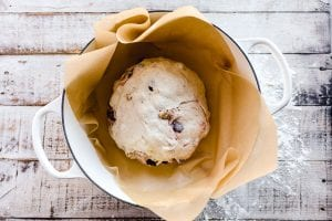 no knead bread ready to bake in parchment paper lined Dutch oven