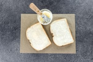 spreading a butter/mayo mixture on bread