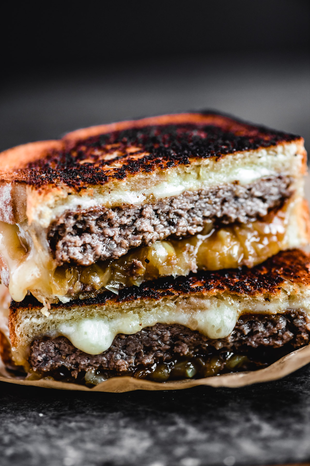 Halves of classic patty melt sandwich, stacked on a plate with cheese dripping