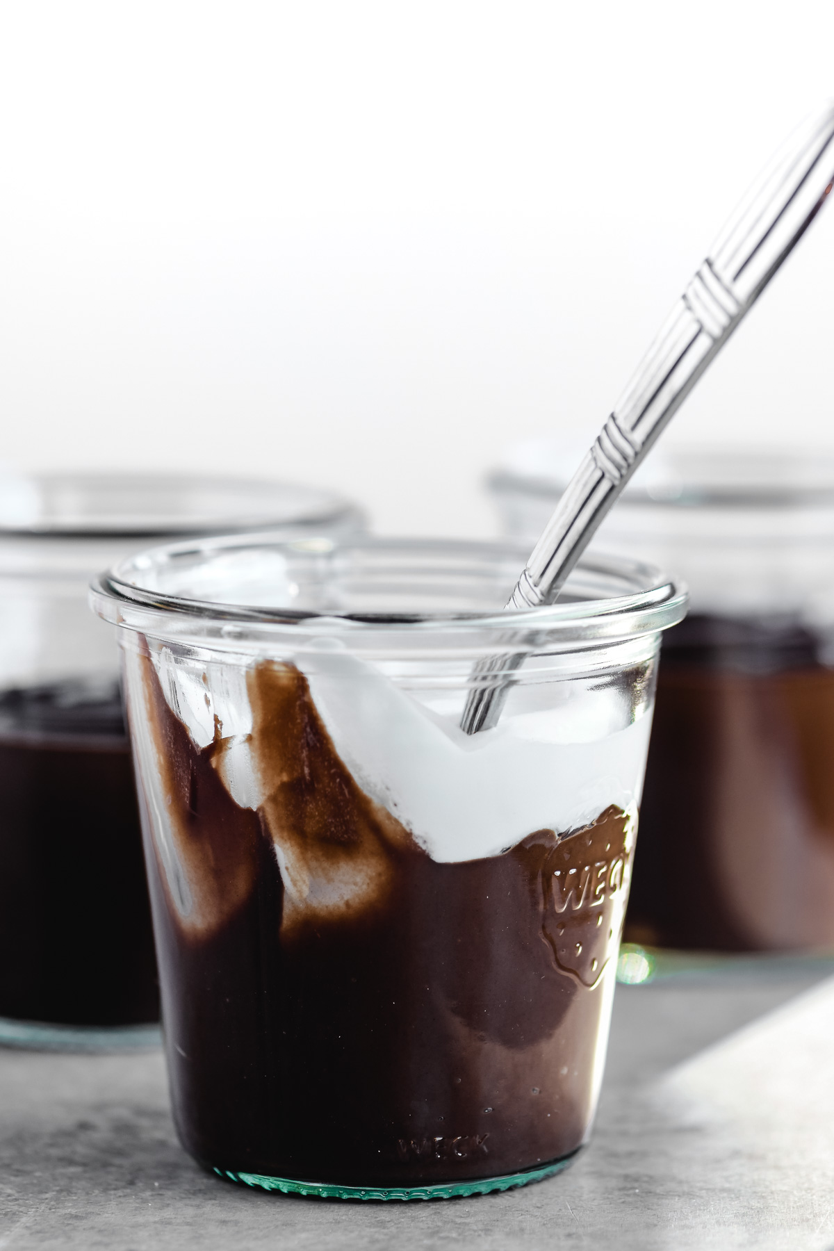 chocolate pudding in a glass jar with whipped cream and spoon