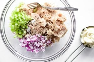 making tuna salad in a glass bowl with fork