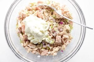 Adding mayonnaise to tuna salad in a glass bowl