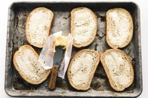 buttered rye bread on a sheet pan