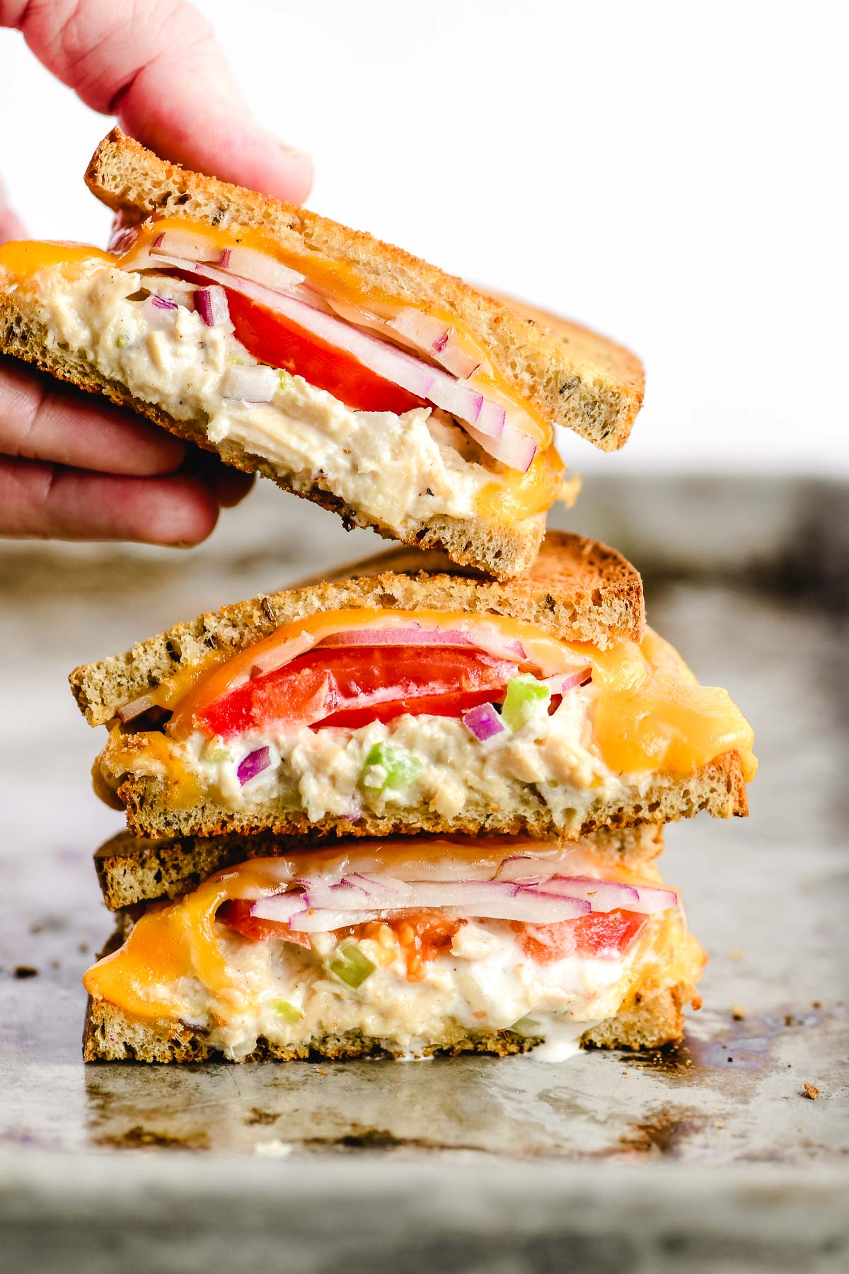 A stack of tuna melt sandwiches on a sheet pan