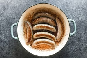 Browning sausages in a cast iron pan