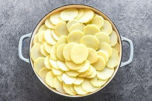 Layering sliced potatoes over top of Irish sausage casserole