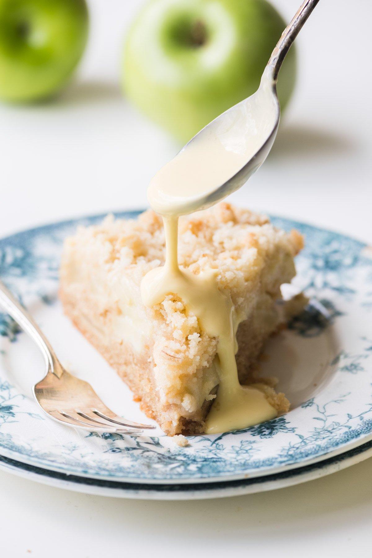 spooning custard sauce on a slice of Irish Apple Cake
