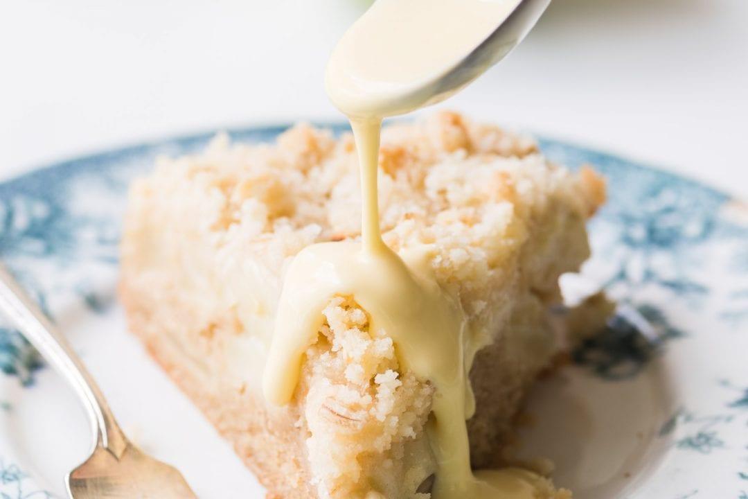 spooning custard sauce on an Irish Apple Cake