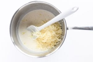 Adding shredded cheese to a gratin sauce
