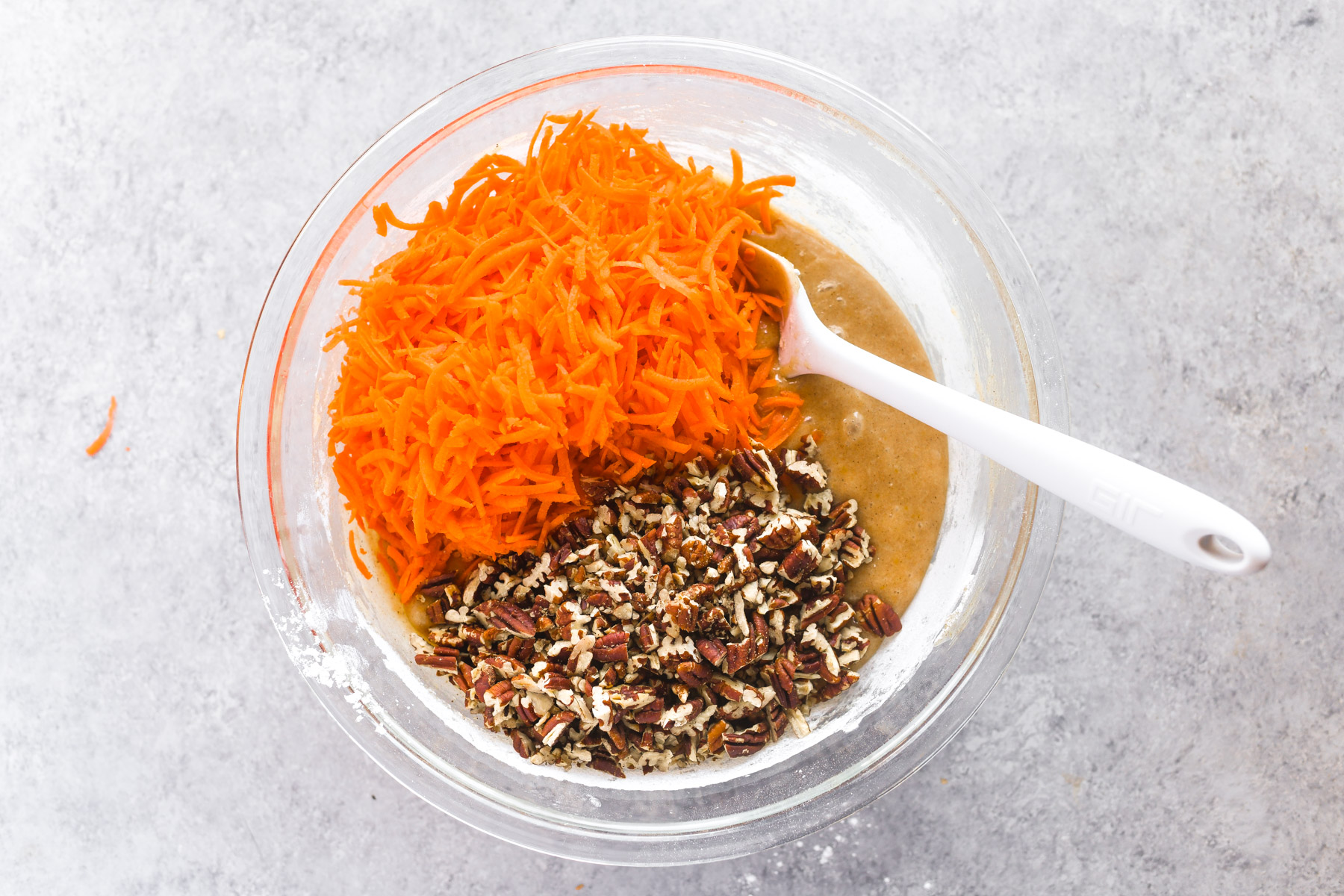 folding in nuts and shredded carrots to cake batter