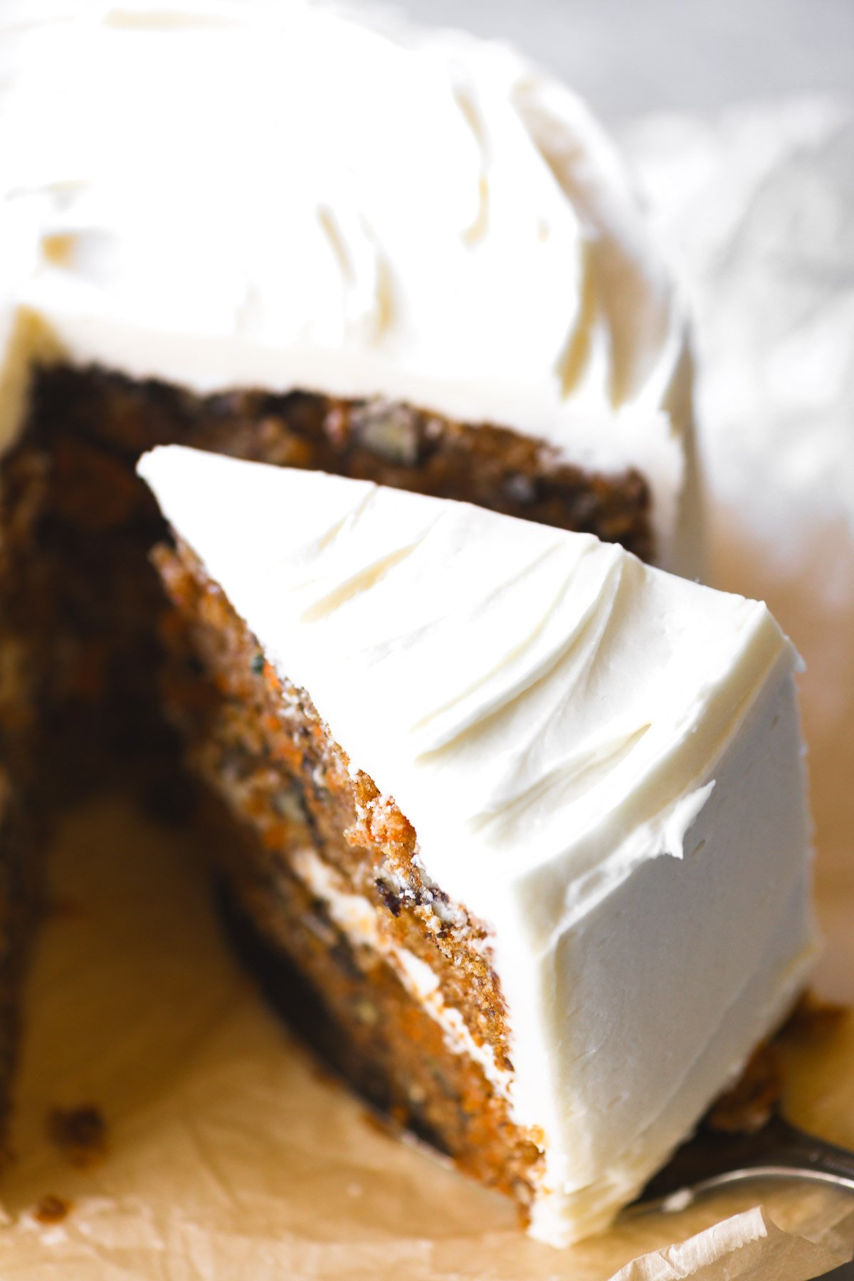 Removing a slice of carrot cake with cream cheese frosting