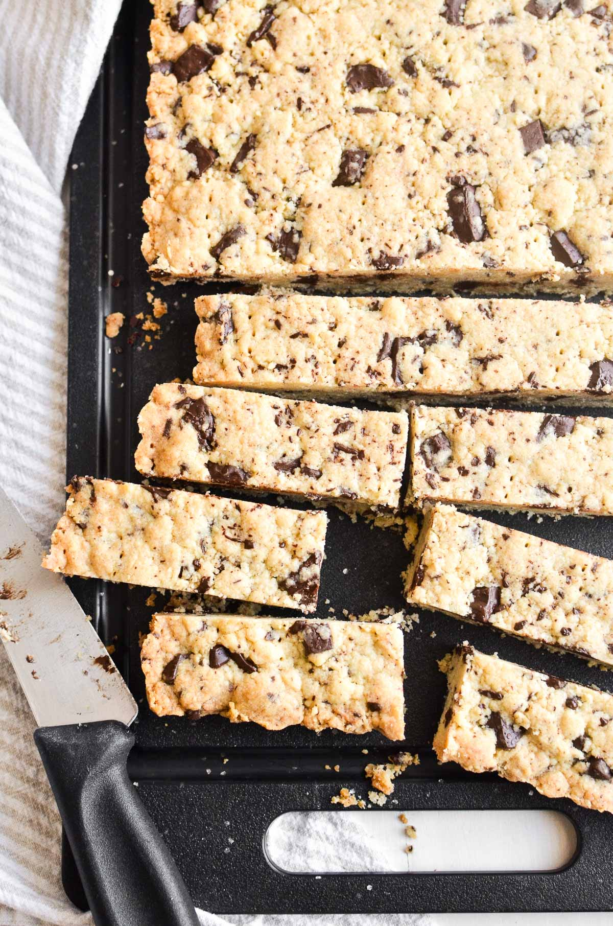 Slicing chocolate chip shortbread cookies on a black cutting board.