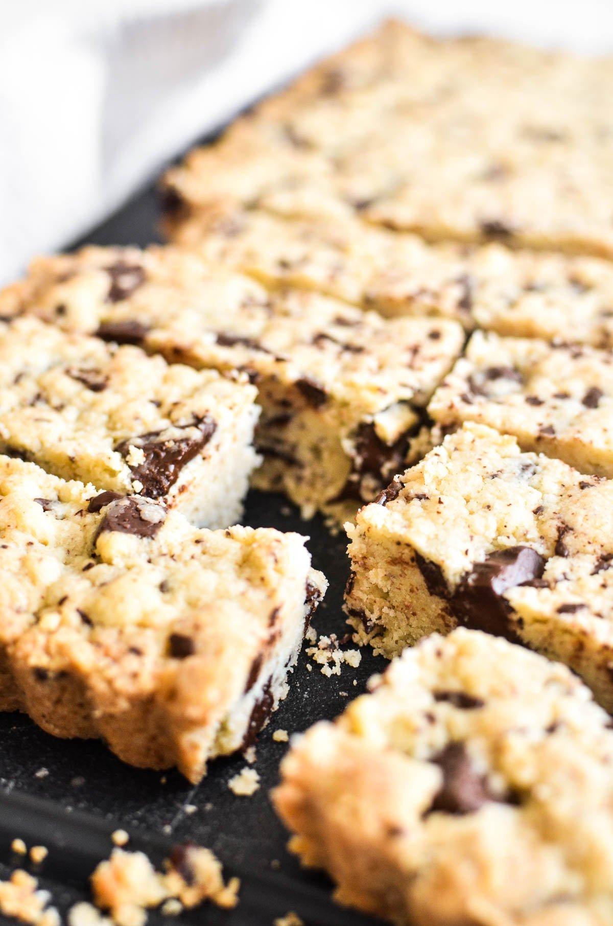 Chocolate chunk shortbread cookies on a black cutting board.