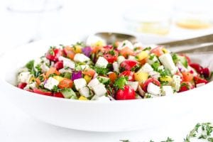 A colorful Israeli salad in a white bowl