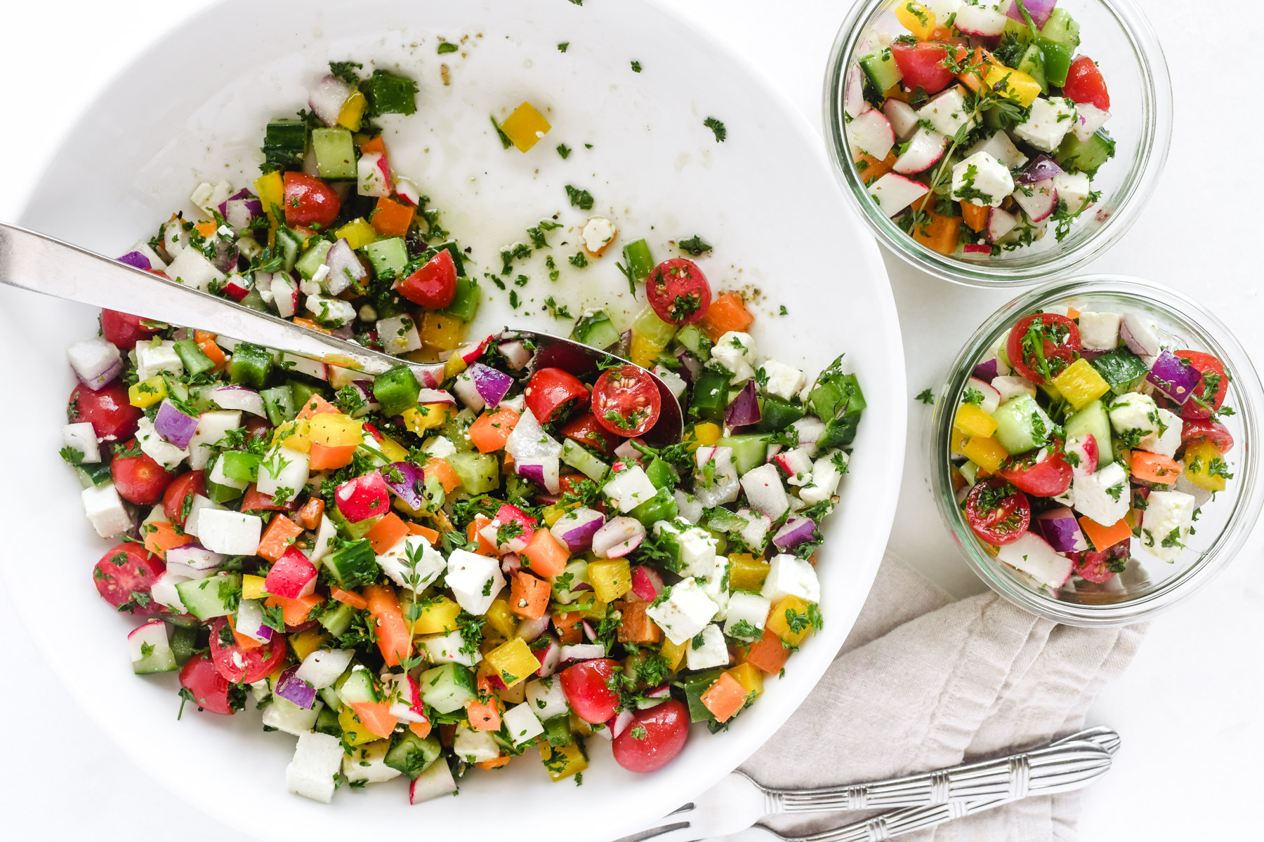 Israeli salad in a bowl with spoons
