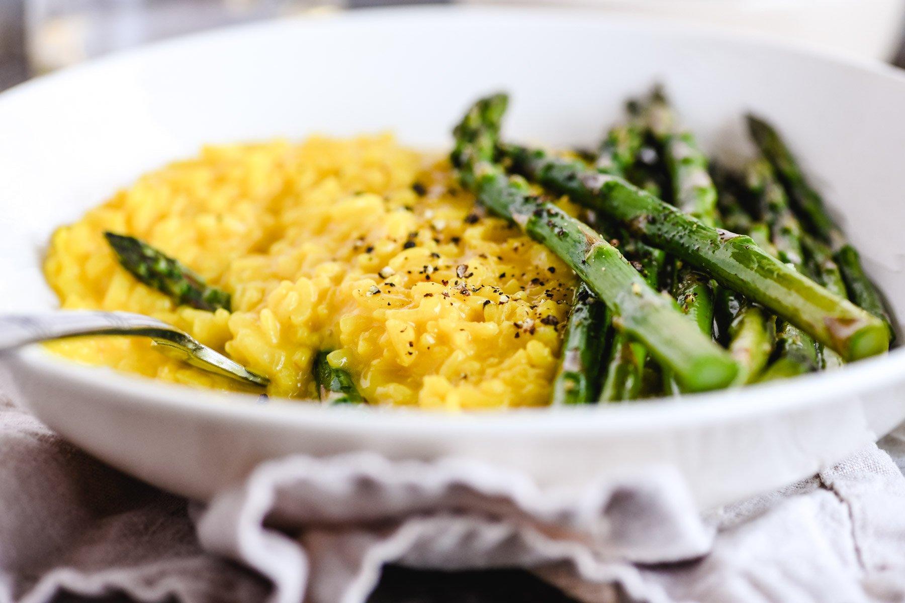 a bowl of saffron risotto and asparagus