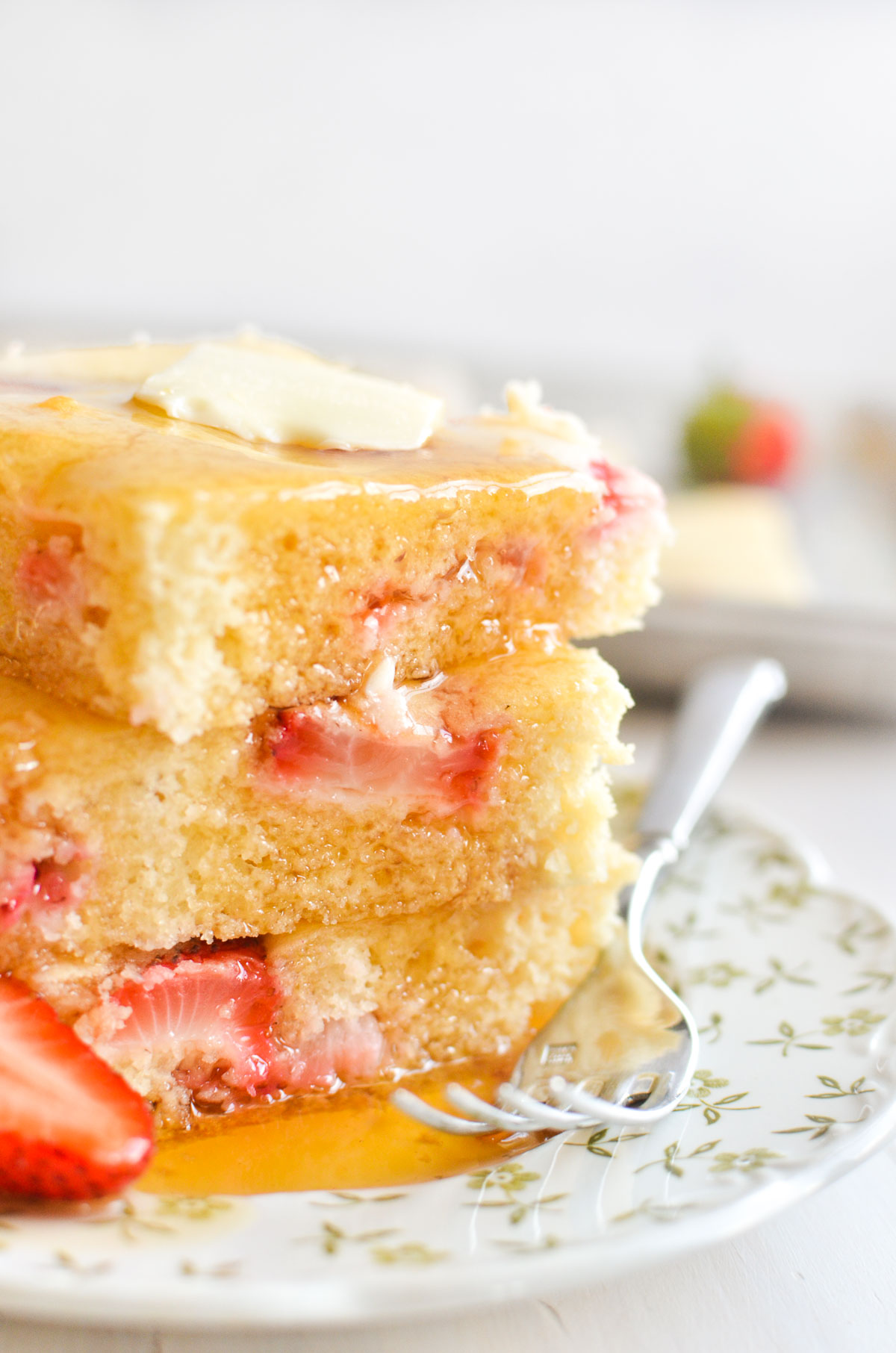 a stack of strawberry sheet pan pancakes with butter