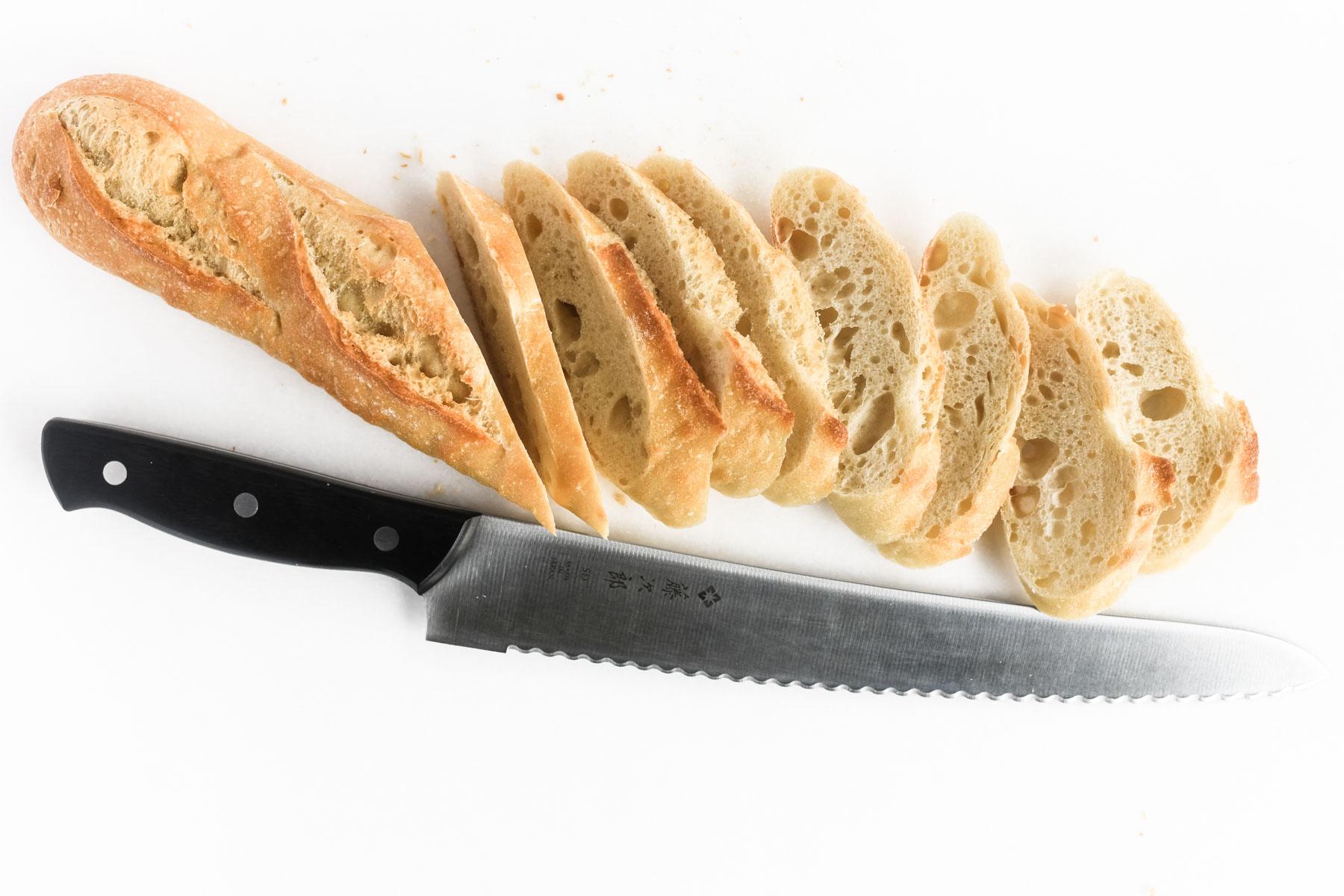 a baguette being sliced for bruschetta