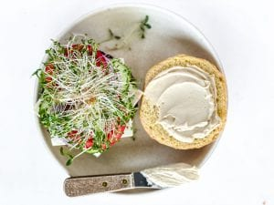 making a falafel burger with sprouts and hummus