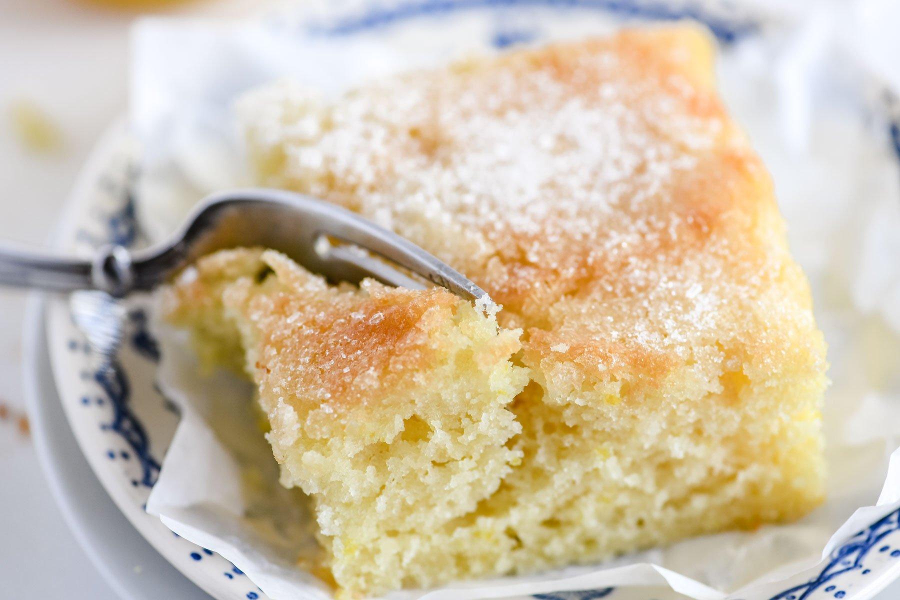 taking a bite of a slice of lemon crunch cake