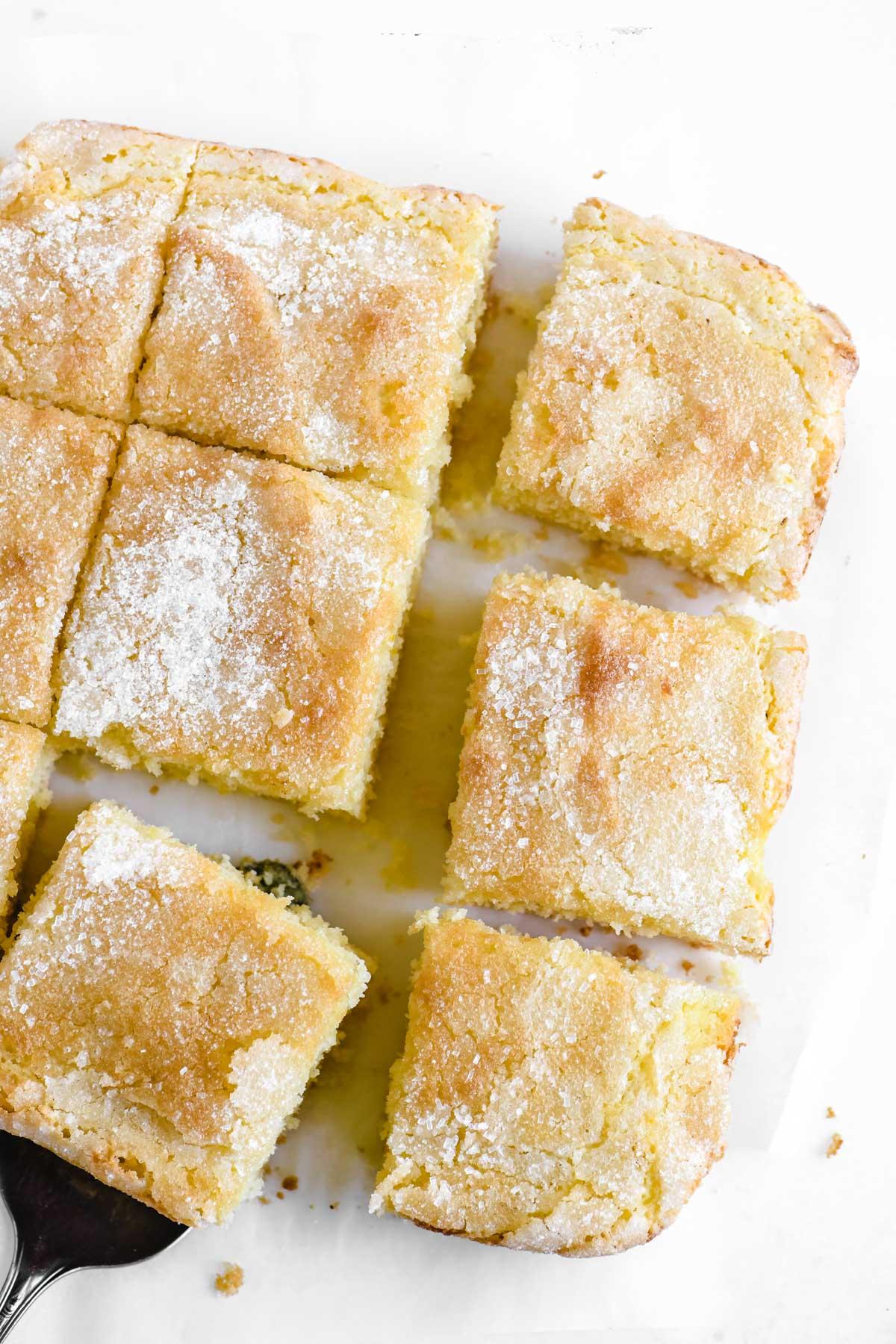 a lemon crunch cake, sliced, on parchment paper