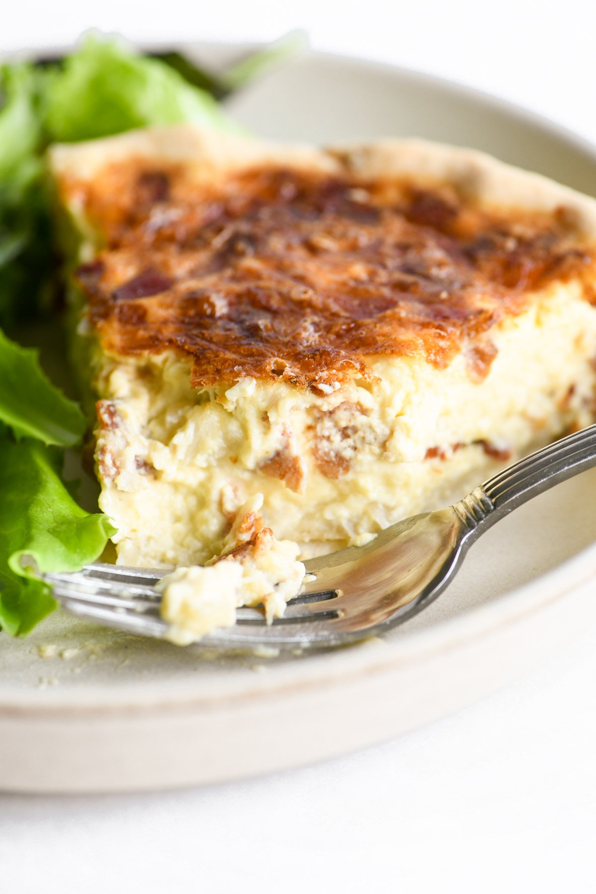 a slice of quiche on a plate with salad