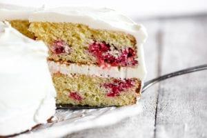 slicing a raspberry lemon cake