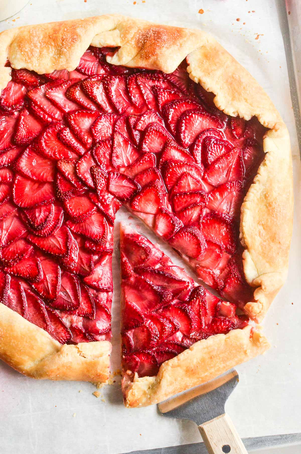Removing a slice of bright pink strawberry galette